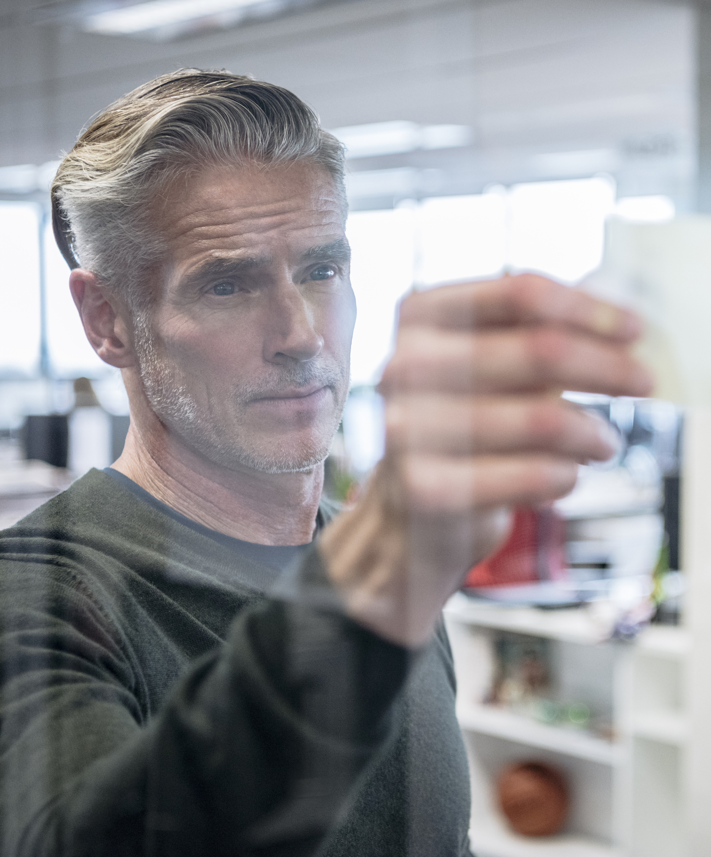 Mature businessman sticking notes on to glass, serious expression